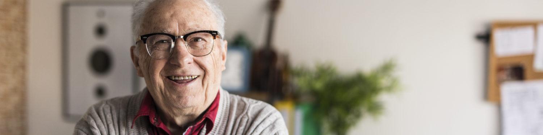 Iäkäs harmaahiuksinen silmälasipäinen mies hymyilee.