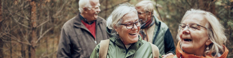 Neljä ikääntyvää, hymyilevää ihmistä kävelee metsässä.