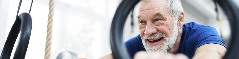 Iäkäs, hymyilevä, harmaahiuksinen parrakas mies pitää kiinni voimistelurenkaista.