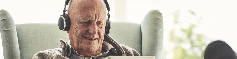 Iäkäs mies kuulokkeet korvillaan.