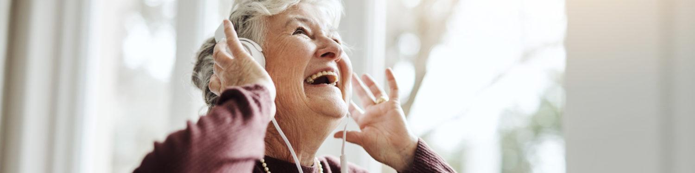 Iäkäs, hymyilevä, harmaahiuksinen nainen katsoo kuulokkeet korvillaan ylöspäin.