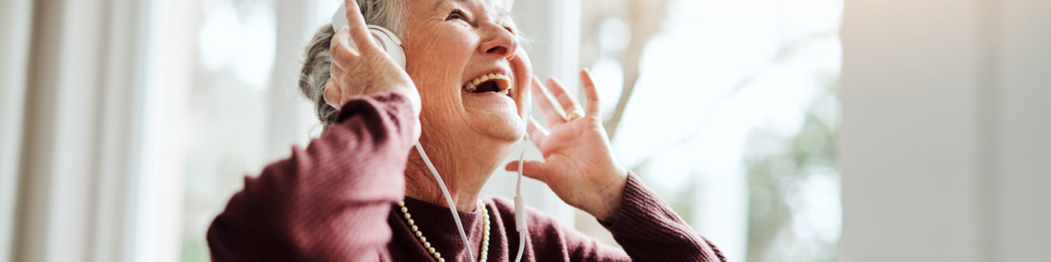 Shot of happy senior woman listening to music with headphones at a retirement home
