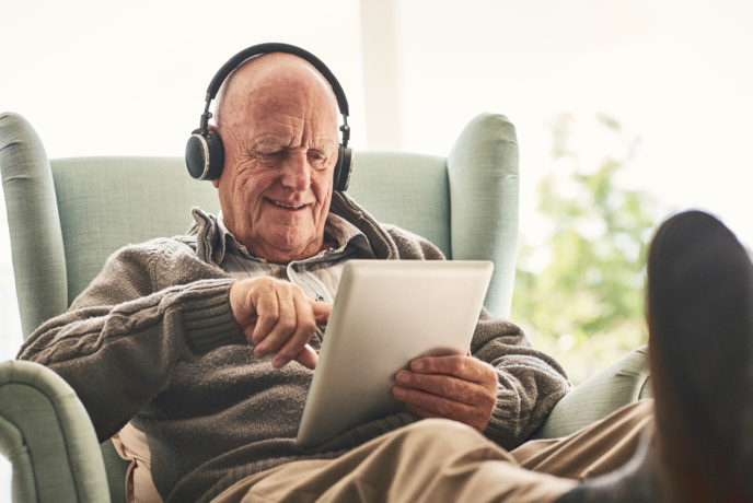 Happy elderly man at home using digital tablet