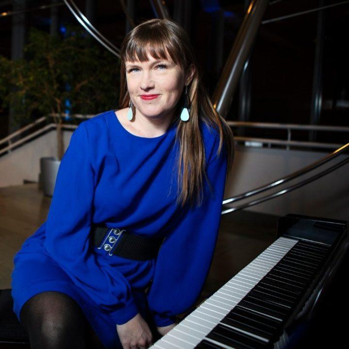 Kati Toikka istuu pianon ääressä.